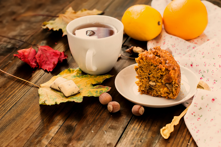 walnut cake: cup of black tea flavored with slices of spicy carrot cake with walnuts The Lake and spices, lemon, walnut kernels, cake on a plate selective focus, toned photo Stock Photo