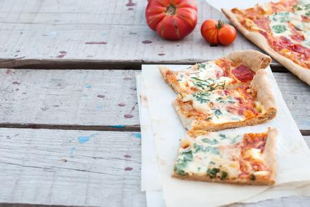 queso rallado: un trozo de pizza con tomates, queso rallado y las hierbas en una placa Foto de archivo