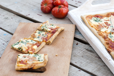 queso rallado: a thin piece of pizza with tomatoes, grated cheese and herbs on a plate