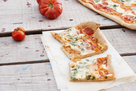 queso rayado: a thin piece of pizza with tomatoes, grated cheese and herbs on a plate