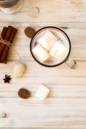 sweet table: Cocoa drink with marshmallows on the wooden table cinnamon sticks, spices, selective focus, toned photo Stock Photo