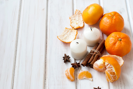 star anise christmas: tangerines, tangerine slices, cinnamon sticks connected, star anise and a white candle - Christmas mood Christmas card on a white background