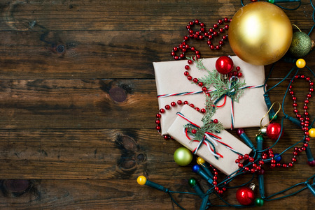 envelope decoration: Christmas gifts decorated kraft paper, berries and fir branches, Christmas decorations, balls and garland on a wooden background Stock Photo