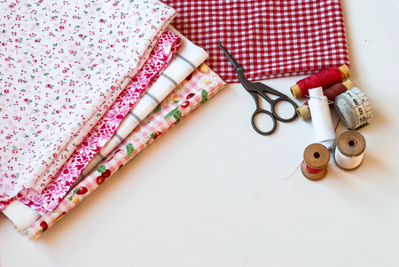 antique table: bright fabrics, antique scissors and spools of thread on a table needlewoman Stock Photo