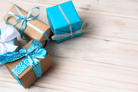 Four gift boxes in wrapping paper with ribbons lying on a white wooden background, selective focus, toned photo
