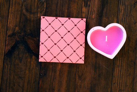bougie coeur: pink heart candle and a gift on a dark wooden background, greeting card Valentines Day