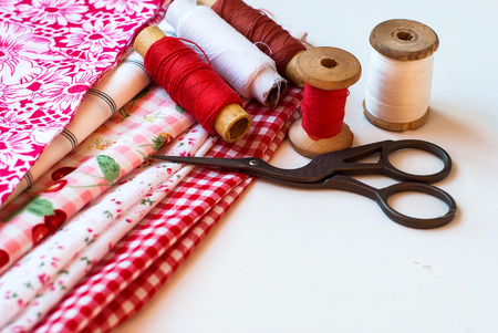 needlewoman: bright fabrics, antique scissors and spools of thread on a table needlewoman Stock Photo