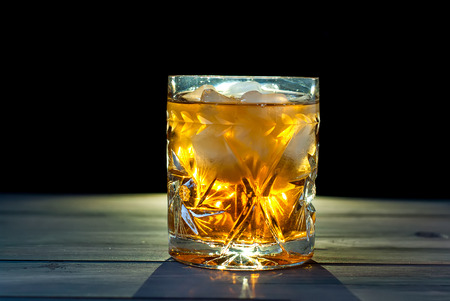 crystal glass: crystal glass of whiskey with ice on a wooden table on a dark background Stock Photo