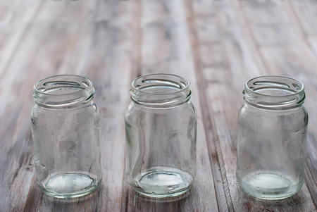 jar: three empty small jars for yogurt on a wooden table