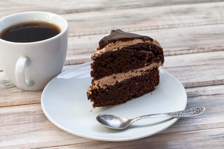 chocolaty: piece of chocolate cake with chocolate topping and cup of tea on the table Stock Photo