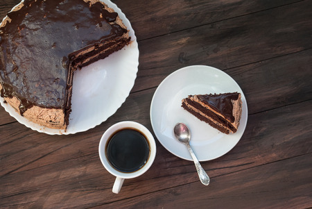 chocolaty: piece of chocolate cake and cup of tea on the table and a big cake with chocolate topping on a stand, a top view