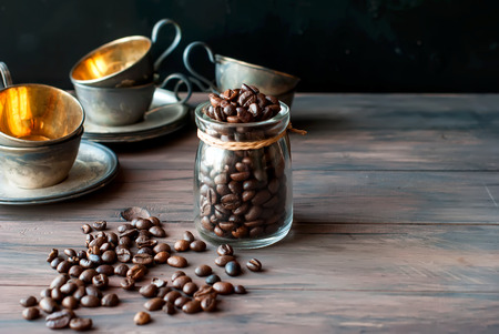 gilt: Coffee beans in a crystal jar on a brown wooden backgroundand old gilt metal coffee cup Stock Photo