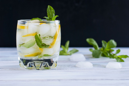 cocktail glasses: glass filled with ice, lemon and mint cocktail ingredients for a mojito on a white table Stock Photo