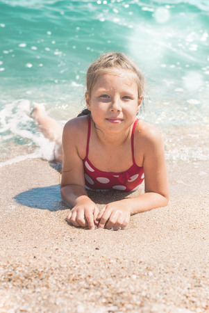 azov: Happy little child, adorable blonde toddler girl wearing colorful swimsuit on the beach Azov Sea