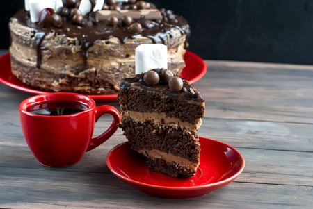 piece of chocolate cake and cup of tea on the table and a big cake with chocolate topping on a stand, Stock Photo