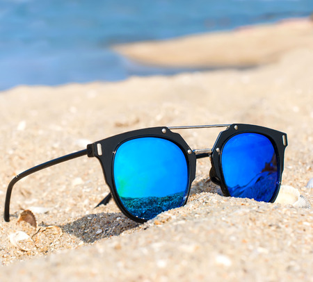 blue mirrored sunglasses on the sand overlooking the sea, the concept of summer beach holidays