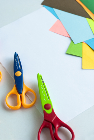 learning by doing: curly scissors and colored sheets of paper for scrapbook classes on a white table. childrens stationery creative tools. Creativity concept.