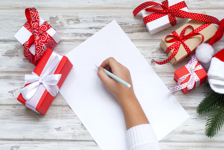 Top view of christmas letter in santa claus hand. Close up of hands holding empty wishlist on wooden table with xmas decoration. High angle view of santa claus hands writing on a paper with gift boxes and fir branch on table.