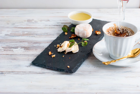 cheese with white mold, mint, honey, walnuts, coffee with milk, breakfast, top view, copy Space Stock Photo
