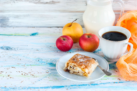 Sweet roll with apple on a plate with sugar cup of black coffee and a jug of milk, apples for breakfast