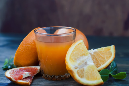 glass of fresh orange juice, whole orange and orange slices group on a dark wooden table