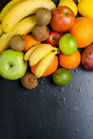 Variety of fresh fruits on dark background from slices of kiwi, bananas, aplle and orange ,copy space