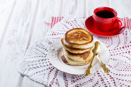 Stack of  homemade pancakes no butter or syrup  in a dish with coffee on wooden white  table, honey and coffee in the background, subdued morning lighting and breakfast setting   Stock Photo