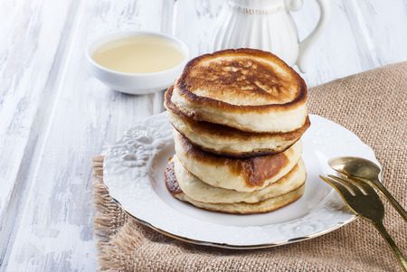 lighting background: Stack of  homemade pancakes no butter or syrup  in a dish on wooden white  table, honey and coffee in the background, subdued morning lighting and breakfast setting