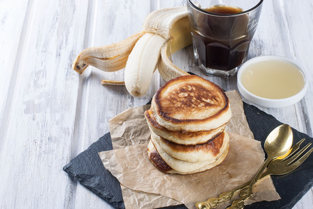Stack of  homemade pancakes no butter or syrup  in a dish with coffee and honey on wooden white  table, honey and coffee in the background, subdued morning lighting and breakfast setting