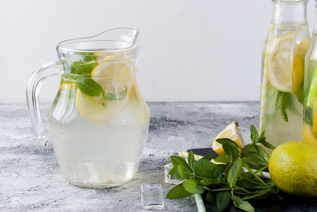 Fresh homemade lemonade in glass jug and bottles with ice and mint.