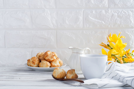 Breakfast, a cup of coffee and eclairs, flowers on a white background