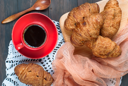 Breakfast with cup of coffee, croissants on dark rustik wooden table, copy space, top view