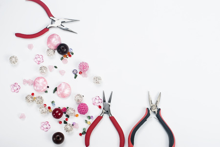 metal fastener: Colorful Beads, pliers,and other needlework  accessories on white background