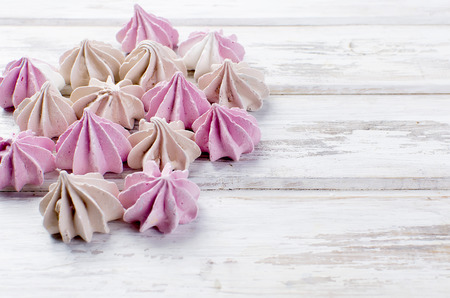Pink and beige  colored french meringues , on white wooden background. Copy space.