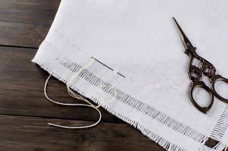 Ricamo. Accessori da cucire. Tela, forbici, ago, filo mouline Archivio Fotografico - 92025048