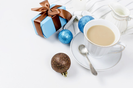 cup of coffee with milk, jug with milk, ball and gifts  for Christmas breakfast on a white background. Serving. Top view, copy space