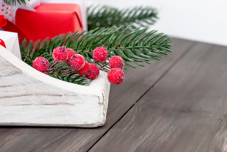 Frozen berryes and Gift box tied, firt branches,candy  on the white background. Christmass card