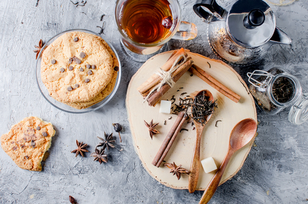dried black tea leaves on a wooden spoon, sticks chinnamon, suger on table. Stock Photo