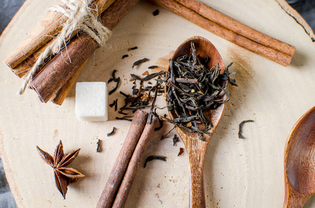 dried black tea leaves on a wooden spoon, sticks chinnamon, suger on table.