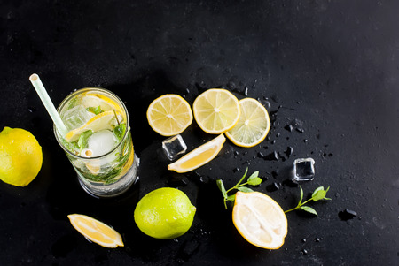 Top view of mojito cocktail, ice cubes and  cocktail ingredients on black slate board, cocktail drinks concept