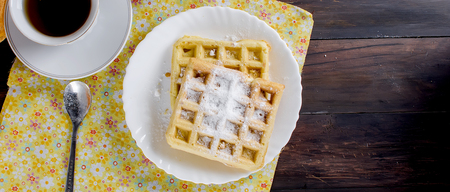 cup of black coffee and viennese waffles sprinkled with powdered sugar  for breakfast on a rustic table. copy space