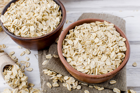 Oat flakes  in ceramic bowl and wooden spoon and spikelets on white vintage wooden background, selective focus copy space, top view