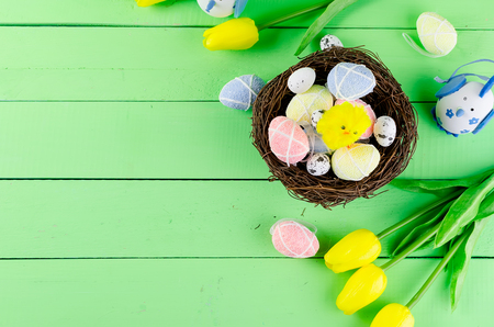 Decorative eggs toys in the nest and tulips for Easter on thelight  green background. Copy space, top view concept of Easter  Stock Photo