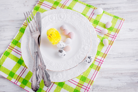 chick and Decorative eggs toys in the plate Place setting. for Easter on the white wooden table. Copy space, top view concept of event Stock Photo