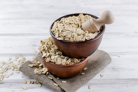 Oat flakes  in ceramic bowl and wooden spoon on white vintage wooden background, selective focus copy space, top view Stok Fotoğraf