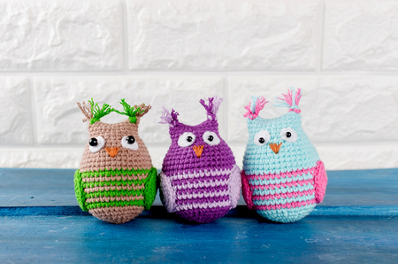 three Cute handmade knitted owls toys on a brick wall background, copy spase
