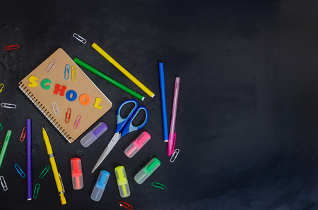 Flat lay with lettering back to school and set of school equipment on blackboard