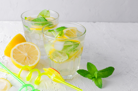 Fresh cold Mojito Cocktail with soda and lemon in glass and ingredients on a light background