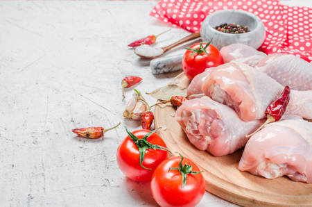 Raw chicken legs on cutting board with fresh parsley and pepper, spices. Food background. Cooking ingredients. Fresh meat.Top view. Copy space.