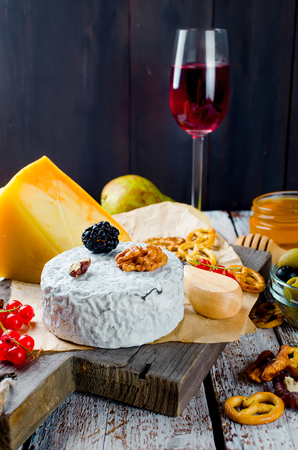cheese sliced, cheese with mildew, hard cheese, olives, walnuts, peanuts, honey, a glass of wine, a romantic dinner, a meal for the shurman